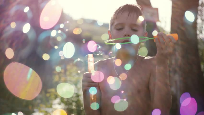 Young handsome happy boy blowing bubbles outdoors on sunny day in summer on sunshine background with blurred magic bokeh. 1920x1080 | Shutterstock HD Video #24109957