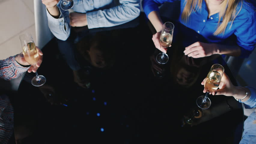 Hands with glasses of wine clink on a black table with reflection. Group of friends in a restaurant celebrating the date. Top view | Shutterstock HD Video #24111514