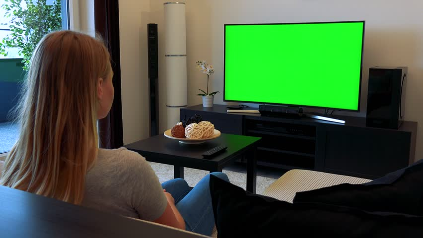 A blonde woman sits on a couch in a cozy living room and watches a TV with a green screen | Shutterstock HD Video #24114178