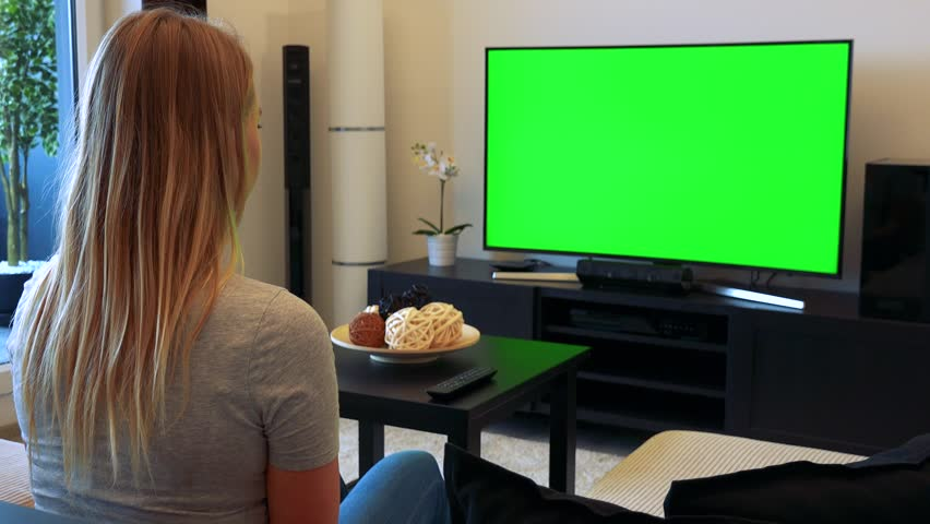 A young, beautiful woman sits on a couch in a living room and watches a TV with a green screen, then turns and smiles at the camera | Shutterstock HD Video #24114205