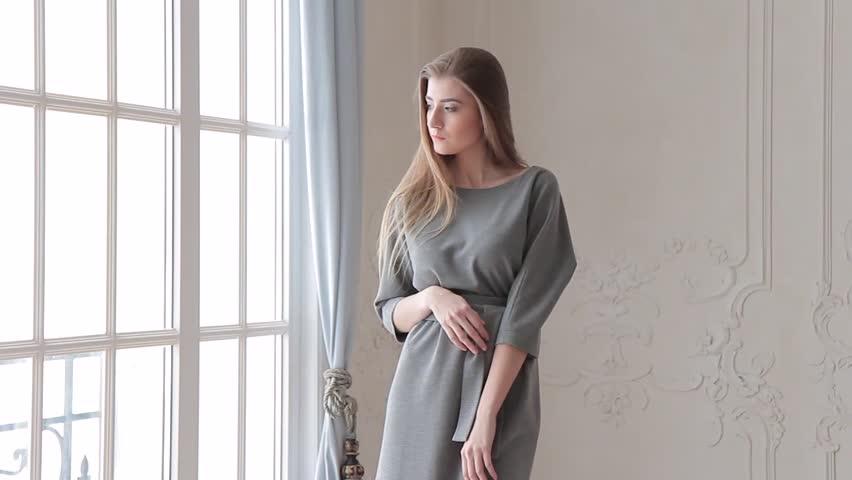 Beautiful fashion model posing in grey dress near window   Shutterstock HD Video #24122692