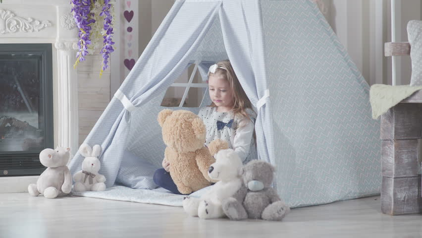 A child plays with toys, talking with them and embraces a soft toy. Little girl in teepee tent. Playroom for kids with Teepee or DIY tent. Wigwam for children in a room. #24129208