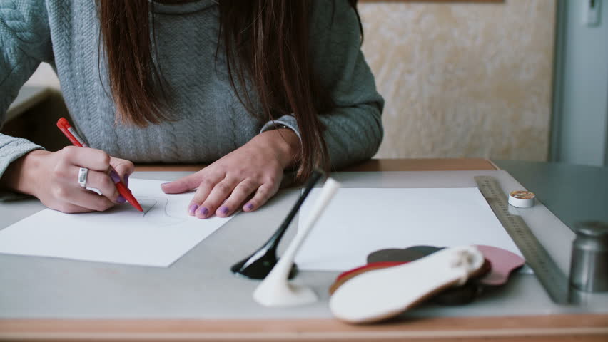 Woman holding pencil, sitting at the table and drawing sketch on paper. Erase in outline. Slider left, front view. 4K | Shutterstock HD Video #24141655
