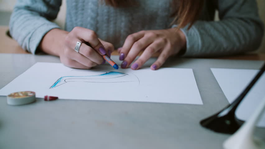 Young designer sitting at table in office, holding pencil and coloring sketch of shoes on paper. Front view. 4K | Shutterstock HD Video #24141664