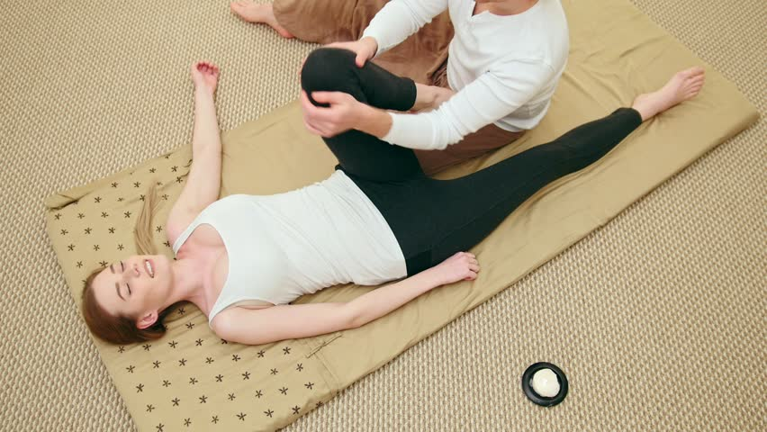 Traditional thailand therapy to hip bone - massage session for white caucasian young woman, top view | Shutterstock HD Video #24147532