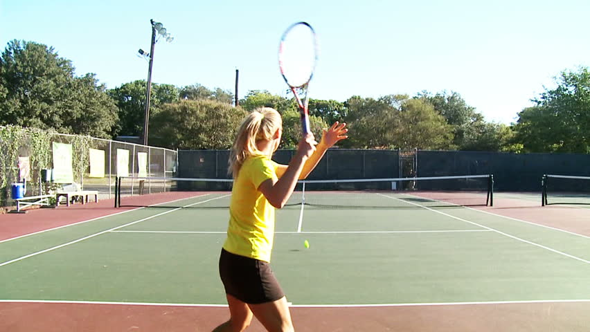 Slow motion of young women playing tennis. Zooming in and out to the ball.