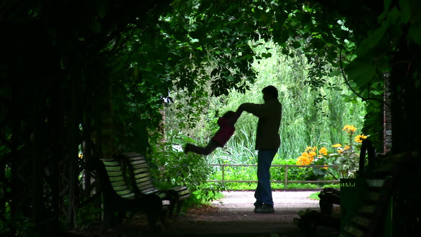 Father Rotatting his Daughter : Silhouette in green arch  - HD stock video clip