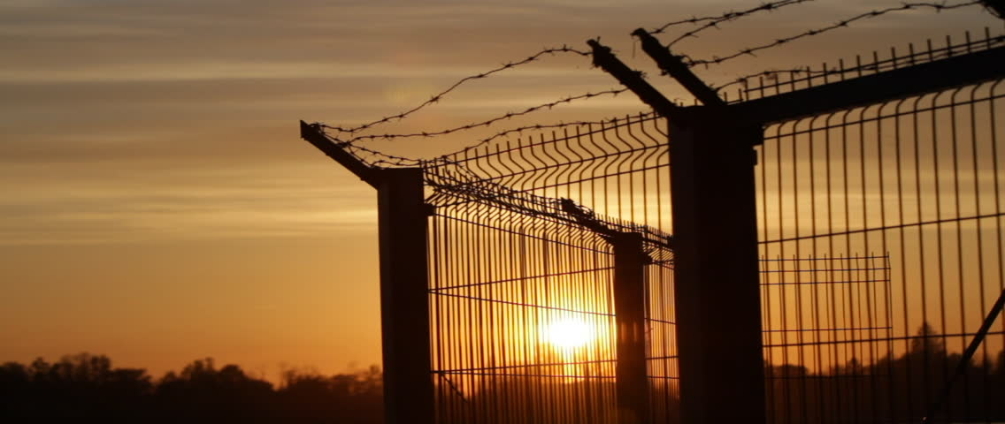 Prison barbed wire fence at sunset. Jet airplane cutting across the sky.