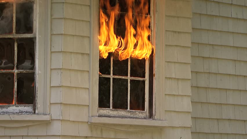 Flames pouring out of window of house on fire - tilt up