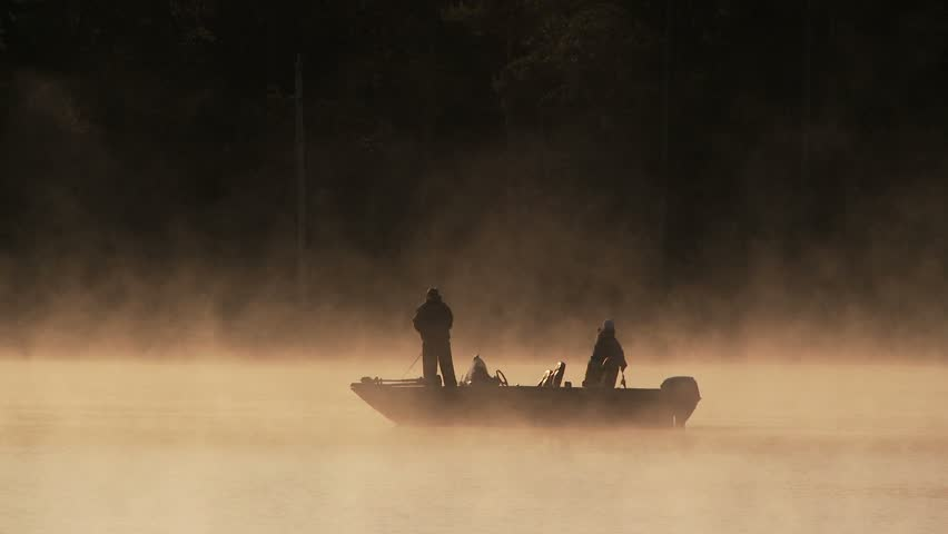 Fog rising from small pond at daybreak with men in small fishing boat