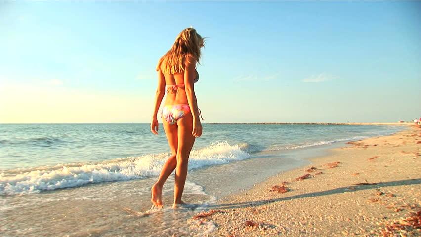 Beautiful blonde girl enjoys a peaceful walk on the beach - HD stock video clip