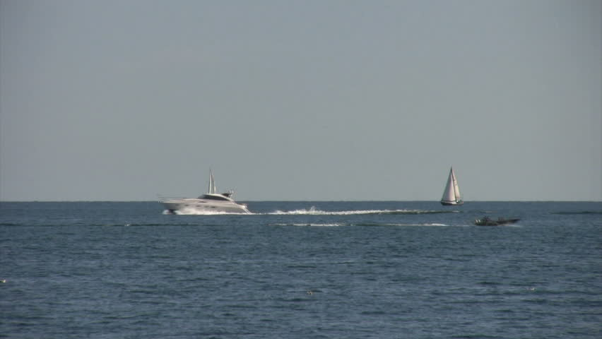 speedboats pass sailboats on lake - 1080i  - HD stock footage clip