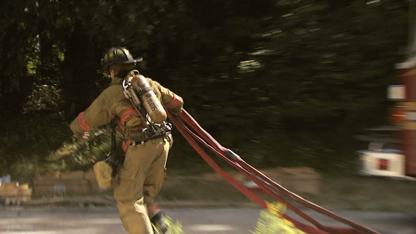 EAST GREENWICH, RHODE ISLAND - CIRCA AUGUST 2010: Fireman running with hoses at house fire