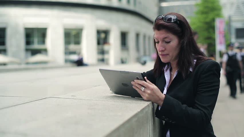 Young businesswoman reading bad news on tablet computer in the city