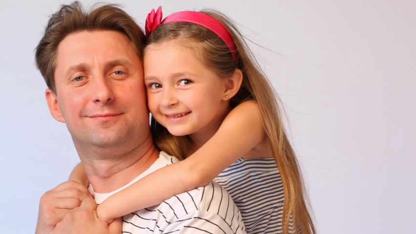 daughter embraces father from back and both smile on white