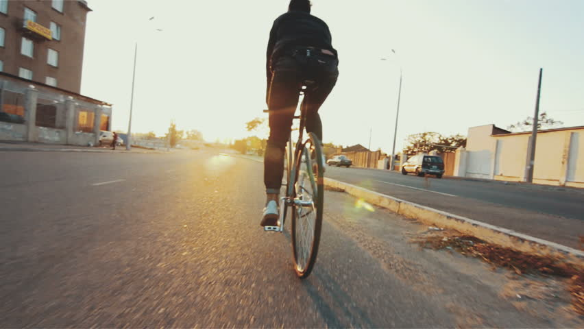 Cyclist man riding fixed gear sport bike in sunny day on a city at sunset | Shutterstock HD Video #26659747