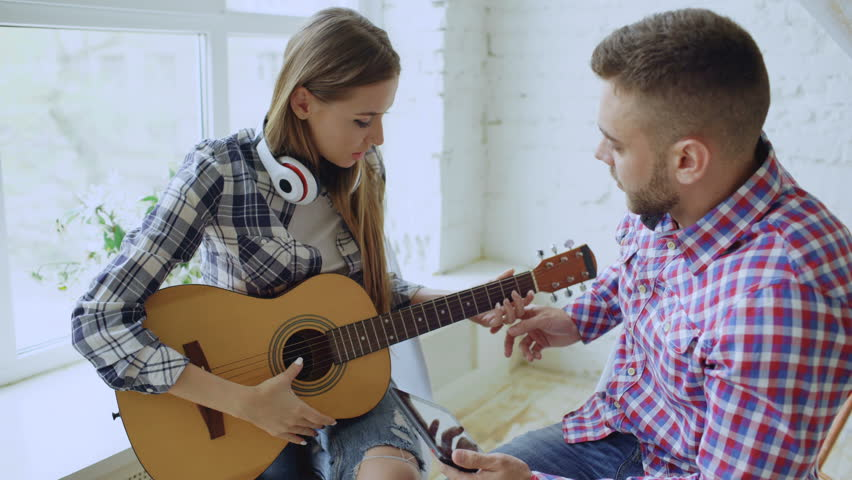 Young happy and loving couple study to play acoustic guitar using tablet computer and having fun while sitting at the table at home | Shutterstock HD Video #26741467