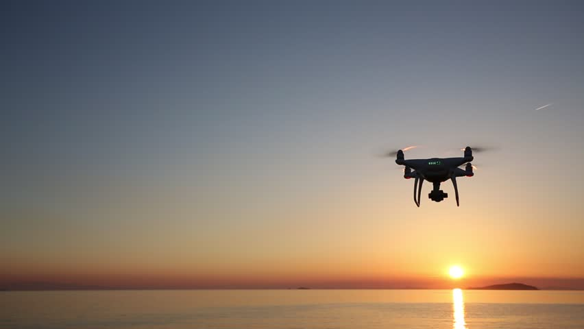 KAGAWA, JAPAN - May 18, 2017: Remote controlled drone Dji Phantom4Pro equipped with high resolution video camera flying above the sea against a sunset sky.  | Shutterstock HD Video #27159643