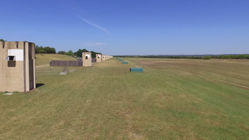 Rising Forward Drone Establishing Shot of Large Field with Sporting Clay High Houses | Shutterstock HD Video #27184960