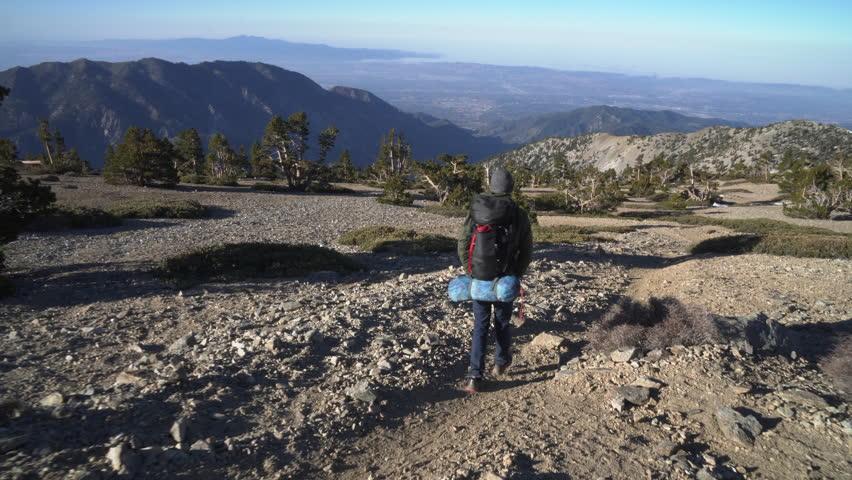 Backpacker walking down a big mountain | Shutterstock HD Video #27193753