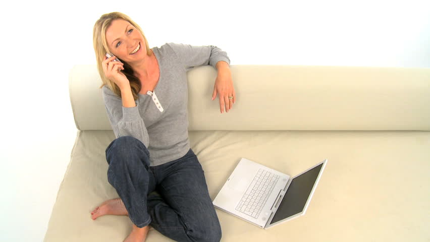 Attractive blonde female using a laptop & mobile phone at home - HD stock footage clip