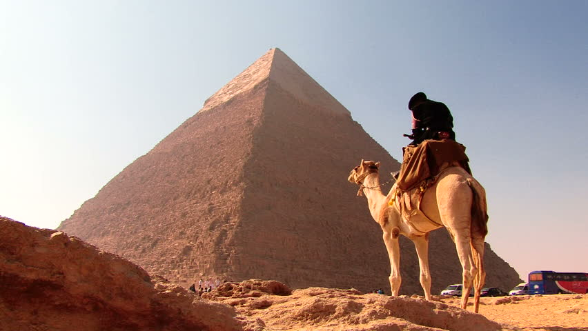 CAIRO, EGYPT - December 2008: Tourists seated at Giza complex on a sunny day with pyramids - HD stock footage clip