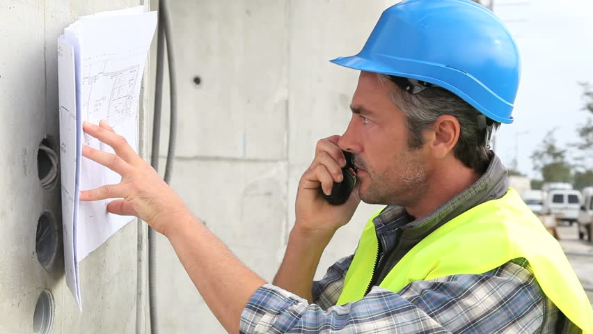 Construction manager using walkie talkie stock footage for How to read construction site plans