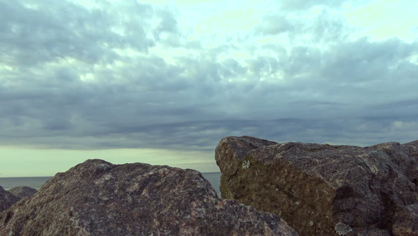 A mystical view of the rocks by the sea and disturbing the sky. Granite boulders from the sea against the sky. Landscape marine nature at sunset. #27681130