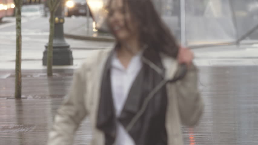 Young beautiful Latin woman dancing around with an umbrella in the city while listening to music. She then walks out of frame | Shutterstock HD Video #27721882