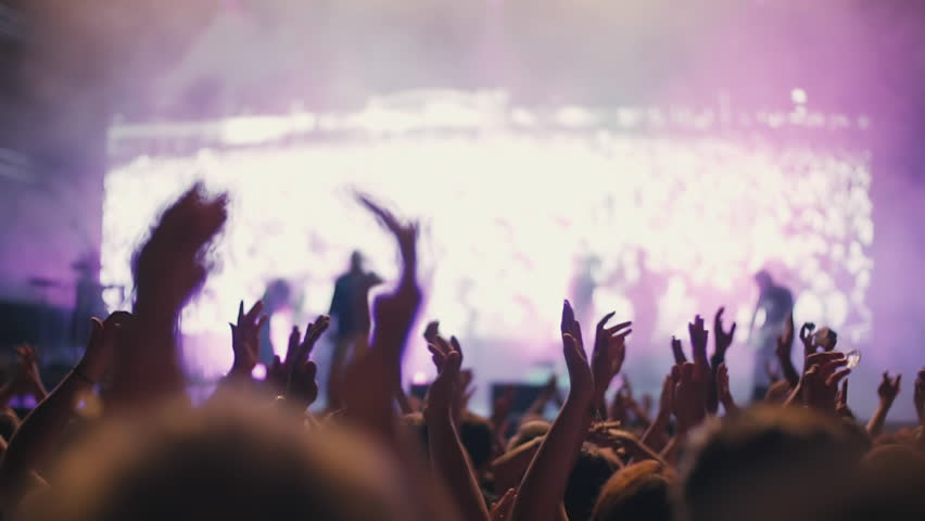 Iconic night rock concert front row crowd cheering hands in air slomo 100p.An outdoor summer night rock concert.People cheer move lift and clap their hands in unison against the strobing stage lights. | Shutterstock HD Video #27821350