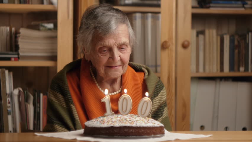 happy grandmother blows 100 candles on a birthday cake