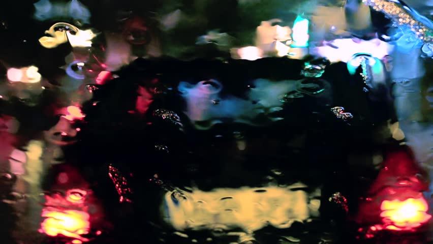 Night city traffic through wet window. Focus on windshield rain drops.