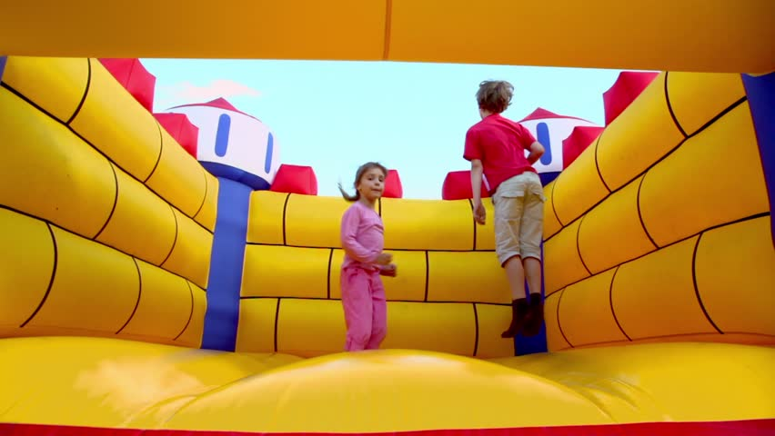 Two kids boy and little girl jump at inflatable playground at sunny summer day - HD stock video clip