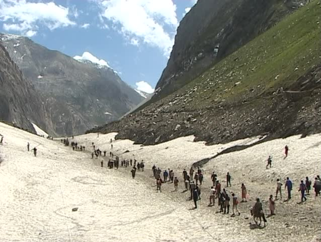 Pilgrimage to the holy Amarnath cave in the Himalayas. Hindu pilgrims crossing snow field - SD stock video clip