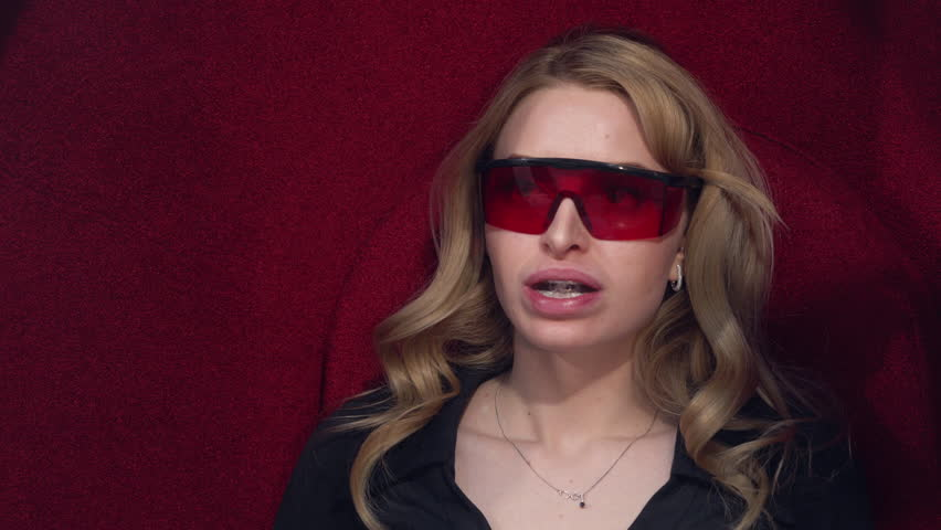 Young blonde girl puts on protective glasses getting UV whitening. Before the procedure of teeth whitening. 4K. | Shutterstock HD Video #28058320
