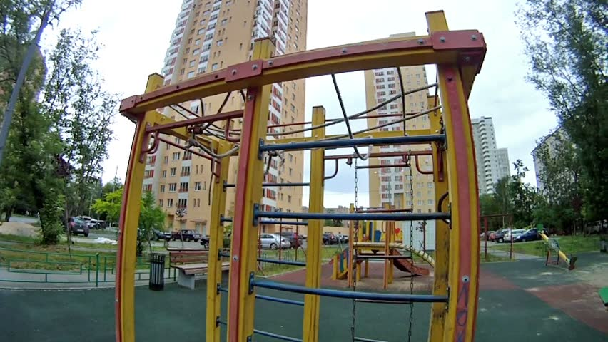 Boy rises on an iron ladder at playground in house yard