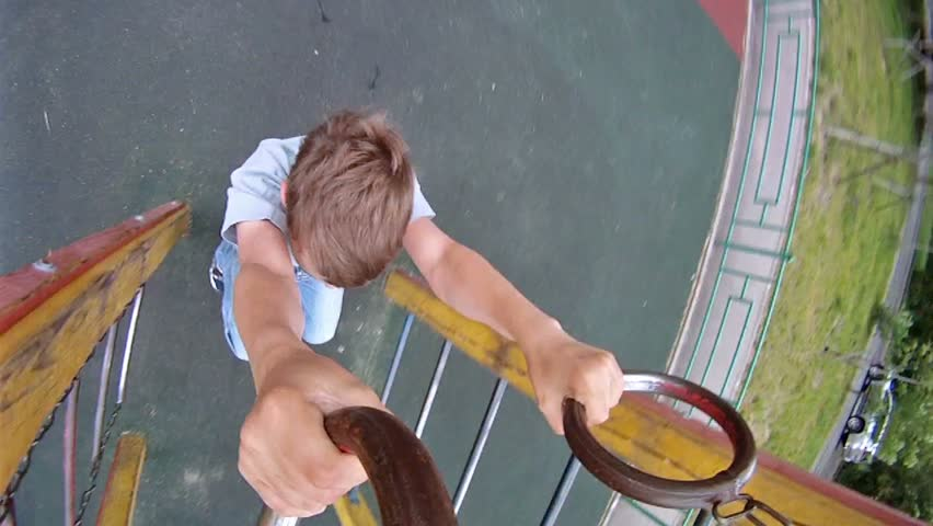 Boy hang on sports rings at playground in house yard