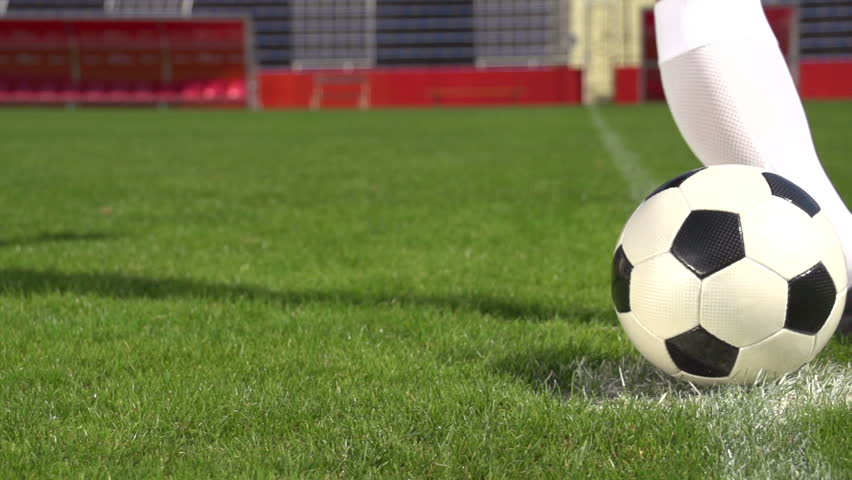 detail soccer player kicking ball on field slow motion
