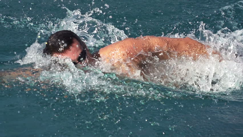 slow motion of professional swimmer swimming the crawl in outdoor pool