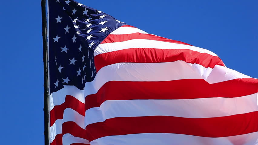 beautiful HD american flag closeup of jumbo flag waving in the gentle breeze with a beautiful blue sky in the background - HD stock video clip