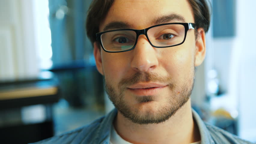 Portrait of young handsome man in blue shirt with glasses working on the laptop in the living room at home while sitting on the sofa. Close up. | Shutterstock HD Video #28459486