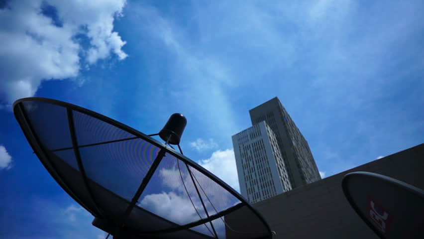 Black antenna communication satellite dish over sky in cityscape - time-lapse - HD stock video clip