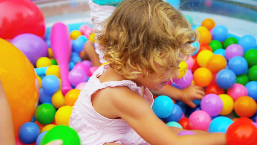 Laughing pre school Caucasian girl in forefront having fun playing with sister ethnic friends in multi coloured ball pool shot on RED EPIC