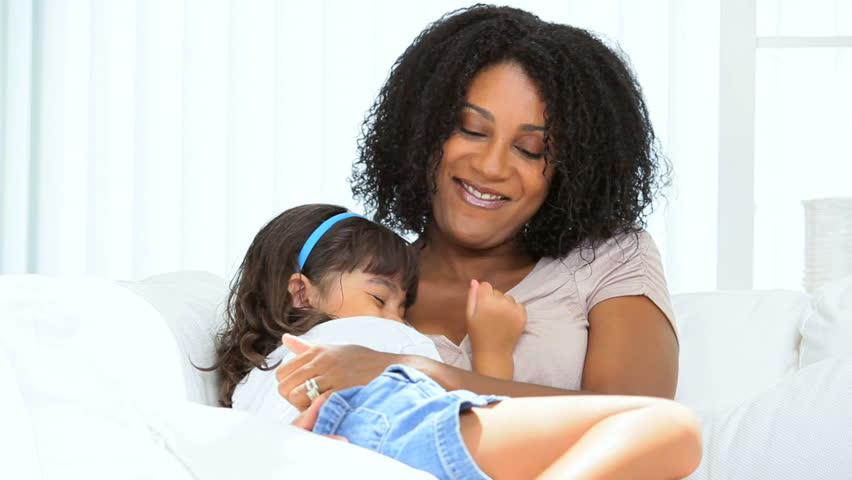 Beautiful young ethnic mother tickling her giggling pre school daughter on home couch