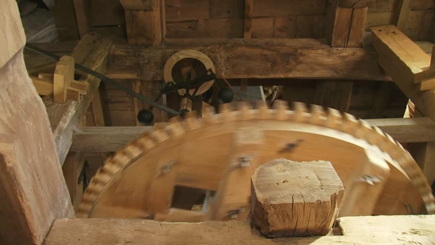 low angle view interior of an industrial windmill - wooden cogwheels and the governor, which automatically adjusts the distance between bedstone and runner stone - HD stock footage clip