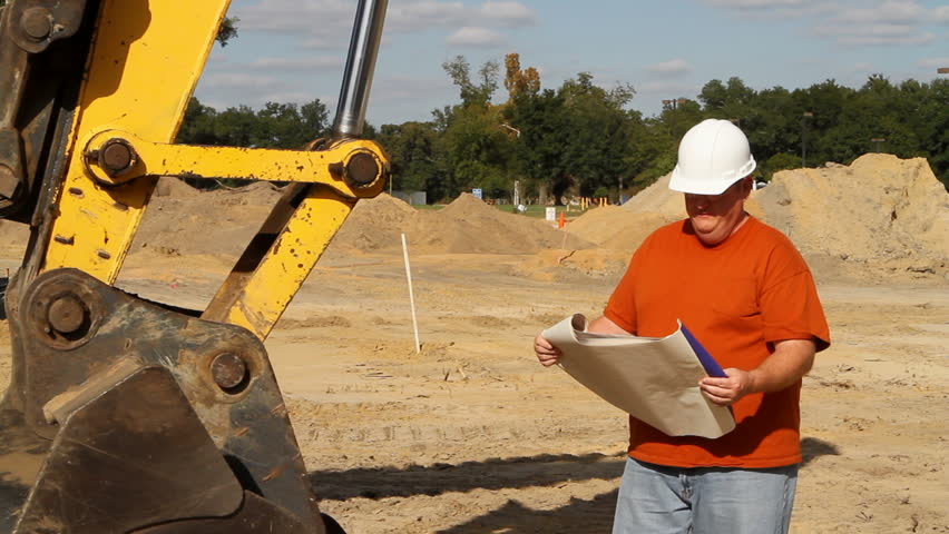 Construction foreman at an excavation site studies some blueprints and surveys the layout of the land. - HD stock video clip