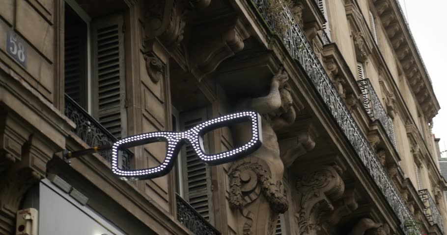 Generic Optometrist eye-wear pair illuminated with led neon sign on the facade of an architecture building in Paris, France | Shutterstock HD Video #29191123