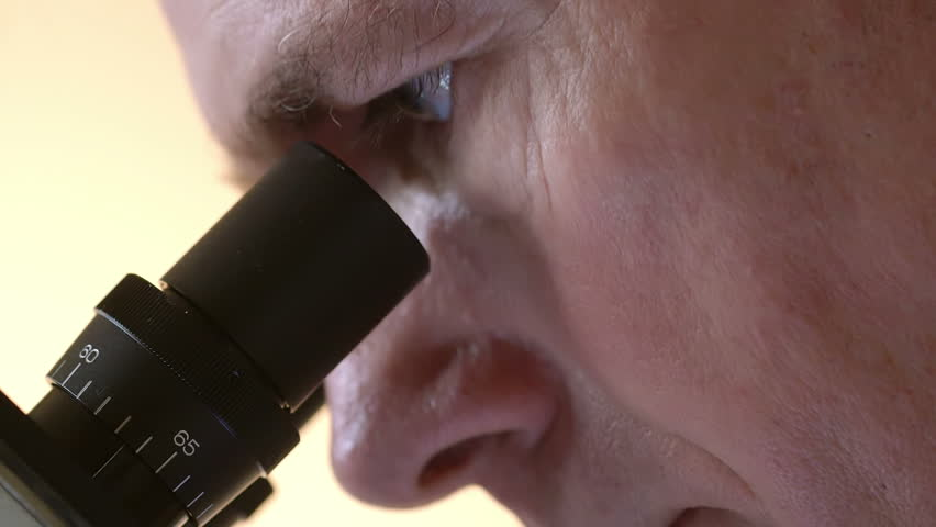 Close up of a mature doctor or laboratory researcher looking through the eyepiece of a microscope. - HD stock footage clip