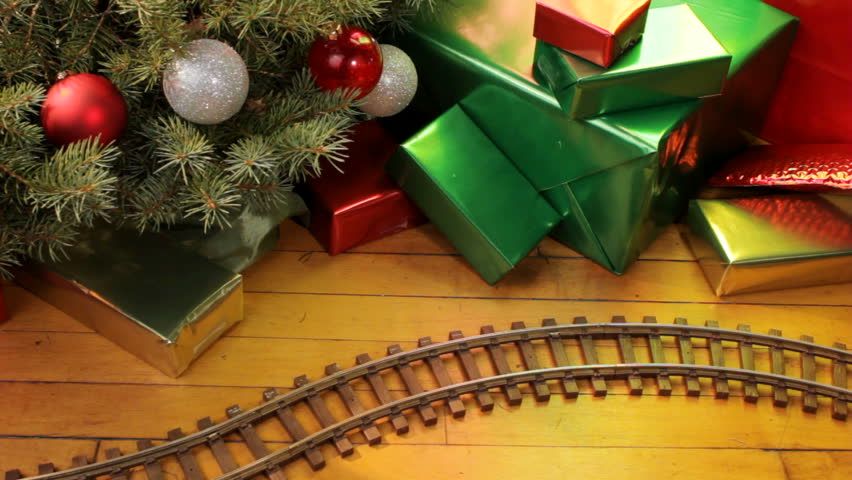 Toy electric train filled with decorations passes along wood floor on Christmas