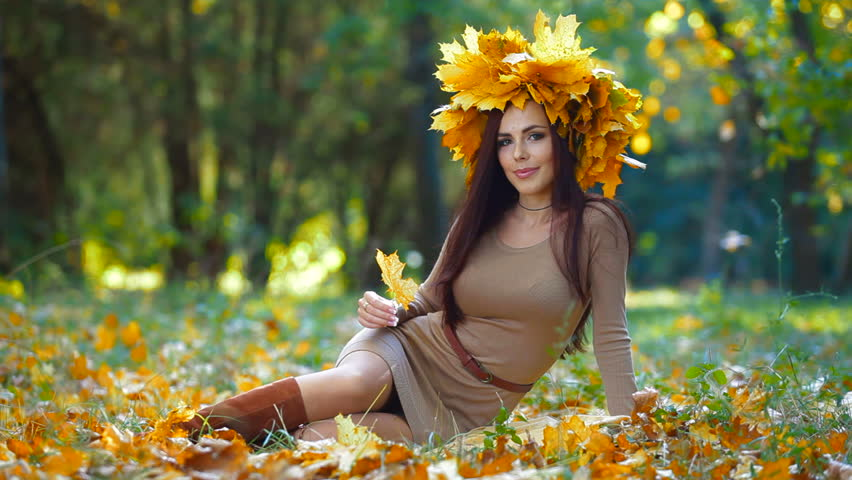 Young attractive woman enjoying autumn day in the park, looking at camera  - HD stock footage clip